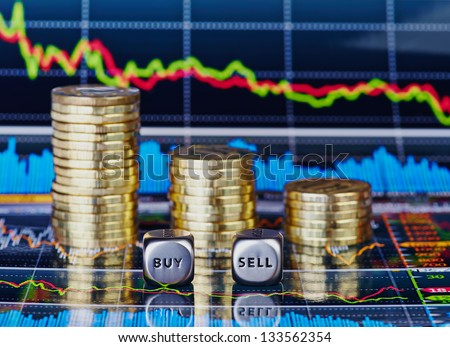 Stacks of coins, dices cubes with the words SELL BUY and down trend chart as the background - stock photo