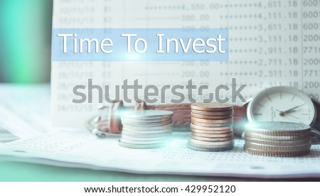Stacks of coins on banking account and vintage watch in the background,color filter,lens flare,text time to invest - stock photo