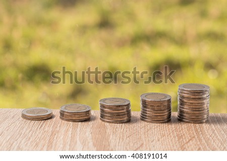 Stacks of coins on wood table with green background - stock photo