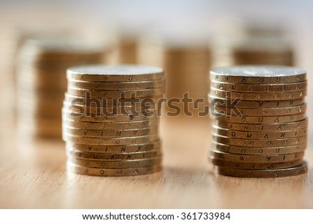 Stacks of coins on wooden table, with selective focus - stock photo