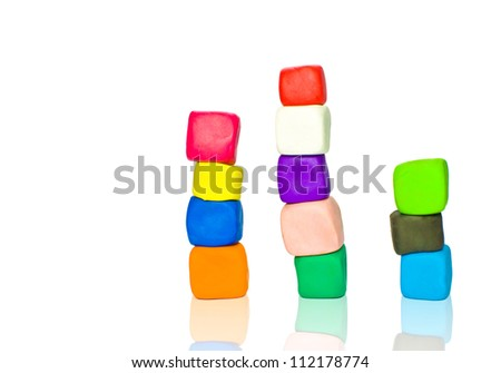 Stacks of colorful plasticine blocks isolated on white - stock photo