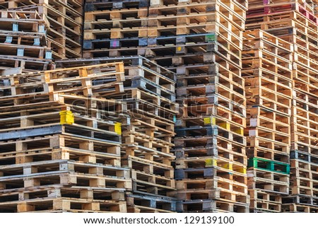 Stacks of colorful wooden euro pallets - stock photo