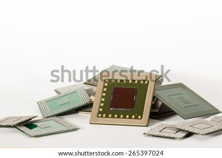 Stacks of computer electronic chips isolated on white. The chips are placed upside down or facing the viewer. There are different chips in the stack from various sizes, shapes and formations. - stock photo