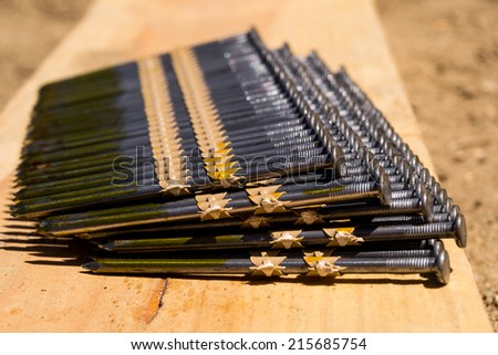 Stacks of construction nails on board. - stock photo