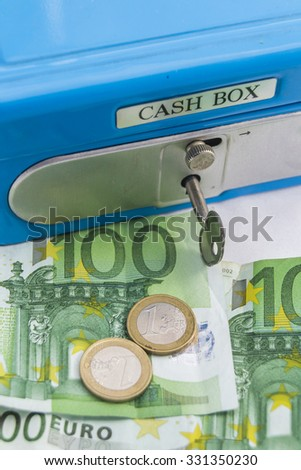 Stacks of euro coins and banknotes in a cash box - stock photo