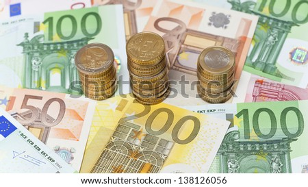 Stacks of  Euro coins on banknote money background.