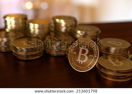 Stacks of gold bitcoins on a table. - stock photo