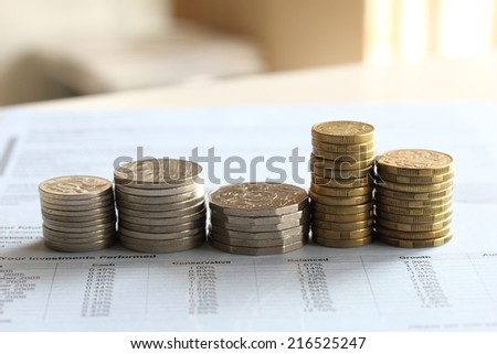stacks of gold coin and silver coin tower shape on business investment finance report blue paper