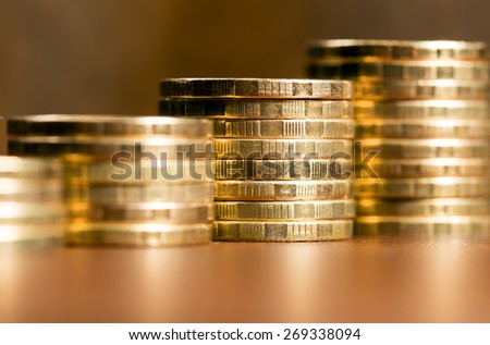 Stacks of gold coins of varying heights - stock photo