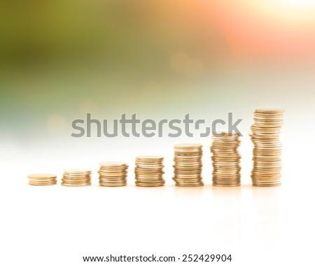 Stacks of golden coins over blurred nature background. Money coin concept. Debt, Money coin, Investment, Insurance Agent, Banking, Saving, Trust, LIT, Planing, Management, ROI, Beginning concept.