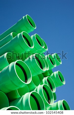 Stacks of green PVC water pipes - stock photo