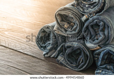stacks of jeans clothing on wood background