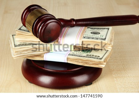Stacks of money and judges gavel on wooden table