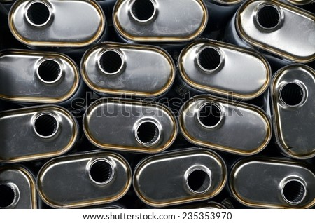 Stacks of new silencers mufflers car before distribution and retail. Detail of a new automotive components in stainless steel. Close up. - stock photo