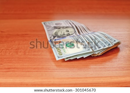 Stacks of one hundred dollars banknotes on wooden desk - stock photo