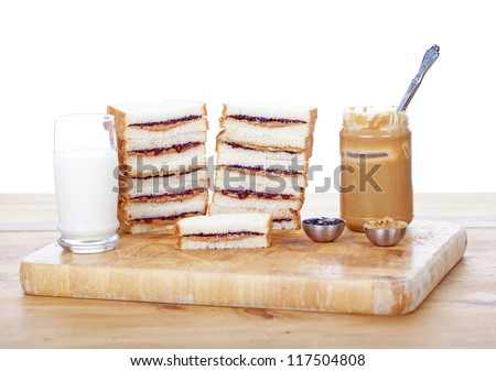 Stacks of peanut butter and jelly sandwiches on white