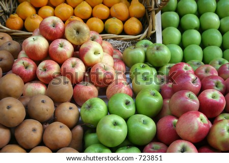 Stacks of pears, apples, and oranges on display at a farmers market.