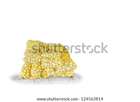 Stacks of potato in yellow netting sack on a timber palette, isolated against white. - stock photo