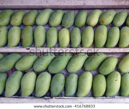 Stacks of sweet aroma ripe green mangoes fruit on wooden stack