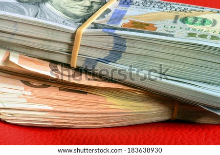 Stacks of ten thousand american dollars and five thousand euro on red leather background. - stock photo
