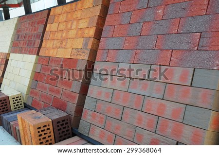 Stacks of various colored concrete pavers (paving stone) or patio blocks organized on  pallets and for sale in a retail setting such as a garden center or building supply. - stock photo
