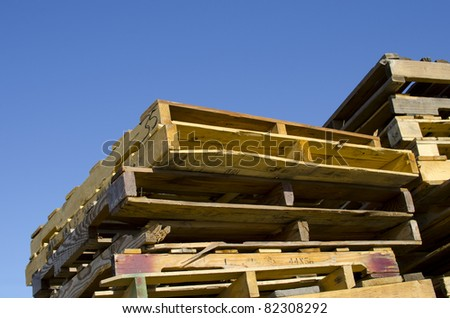 Stacks of worn, well-used wooden pallets at an industrial plant