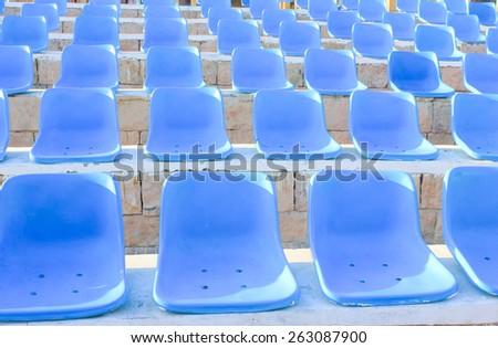 Stadium Blue Chairs at sun light. - stock photo