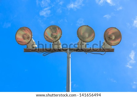 Stadium flood lights at basketball field against blues sky and white cloud - stock photo