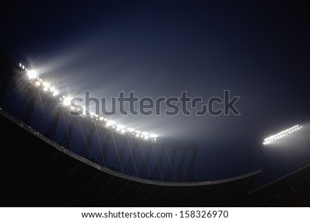 Stadium floodlights at night time - stock photo