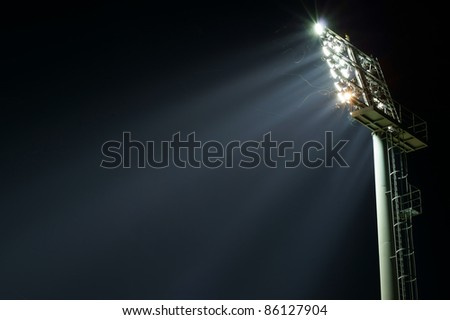 Stadium lights turned on and some insects at night - stock photo