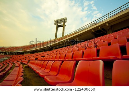 stadium, red seats on stadium steps bleacher with spot light pole - stock photo