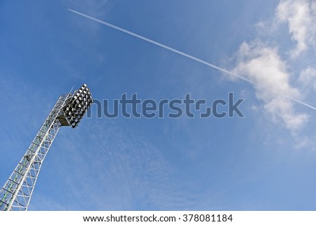 Stadium spotlights with airplane across blue sky in the background