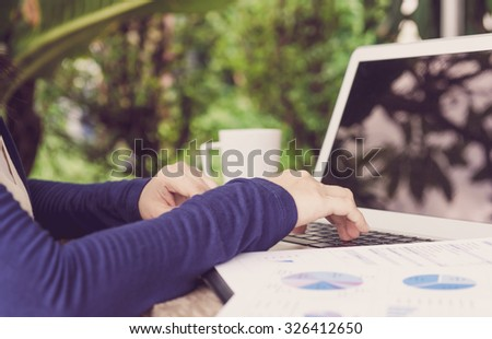 staff analyzing data for marketing strategy with laptop computer on table at garden . view side.  retro or vintage style. - stock photo
