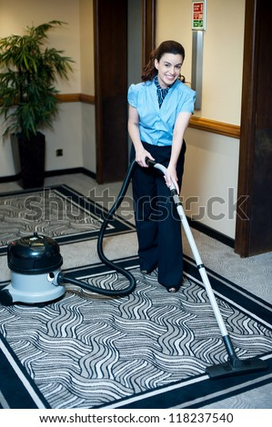 Staff cleaning carpet with a vacuum cleaner. Smiling and enjoying her work - stock photo