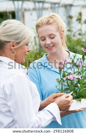 Staff Giving Plant Advice To Female Customer At Garden Center - stock photo
