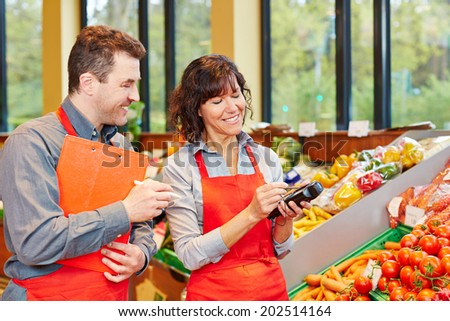 Staff in supermarket using mobile data acquisition terminal for vegetables delivery - stock photo