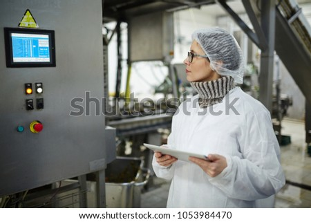 Staff of food factory in protective uniform looking at display with regullation information on wall of industrial machine