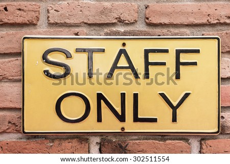 staff only on yellow license plate on red brick wall - stock photo