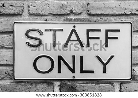 staff only on yellow license plate on red brick wall in black and white style - stock photo