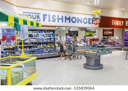 Staffordshire, England. - June 21st 2014 Young family shopping at the fishmongers counter in Morrisons supermarket store. Leek, Staffordshire, England.