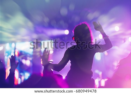 Stage lights and crowd of audience with hands raised at a music festival. Fans enjoying the summer vibes.