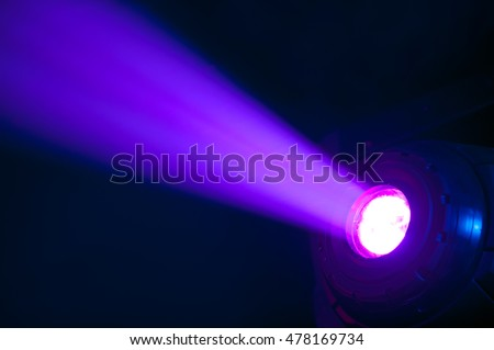 Stage spotlight with purple light beam over dark background