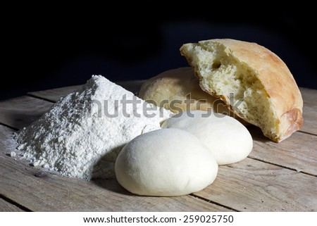 Stages of Making Bread-Flour, Dough and Loaf of Bread on Wooden Table Over Black Background - stock photo