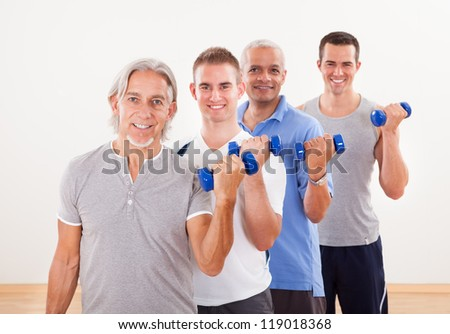 Staggered row of four men of differing ages facing the camera working out with dumbbells at a gym