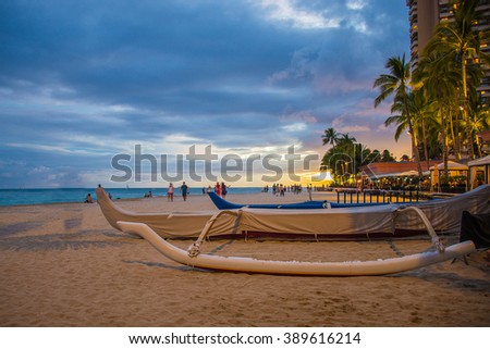 Staggering sunset view from the Waikiki beach with blue skies and a traditional sailing boat docked at the beach. - stock photo