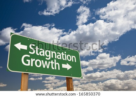 Stagnation or Growth Green Road Sign Over Dramatic Clouds and Sky. - stock photo