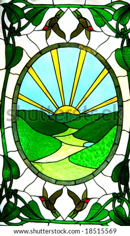Stained glass door has valley in green and a sunrise of yellow.  Birds and leaves decorate outside edges. - stock photo