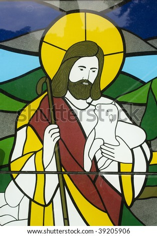 Stained glass image of Jesus with a lamb.  Like a sheppard taking care of his flock.