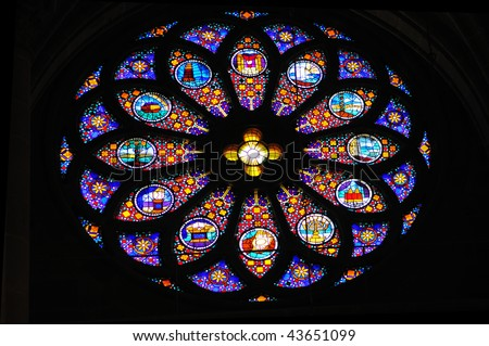 Stained glass rose window depicting bible stories.