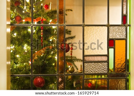 Stained glass window and decorated christmas tree - horizontal - stock photo